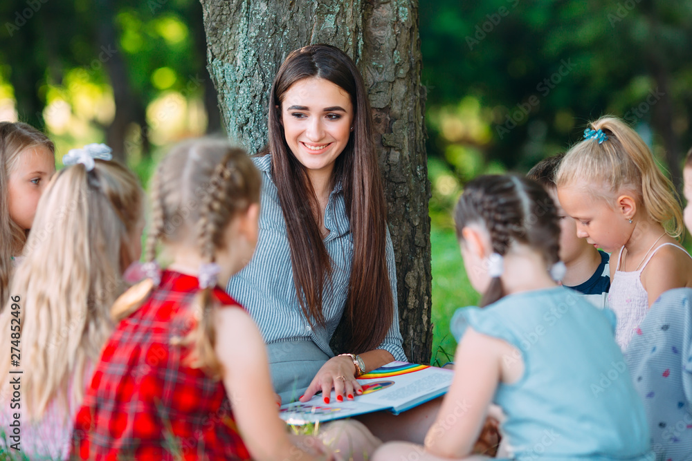 Fototapety, obrazy: Children and education, young woman at work as educator reading book to boys and girls in park.