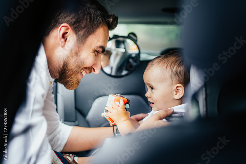 Smiling father putting baby in child seat, fastening seatbelt - Family transportation, lifestyle concept