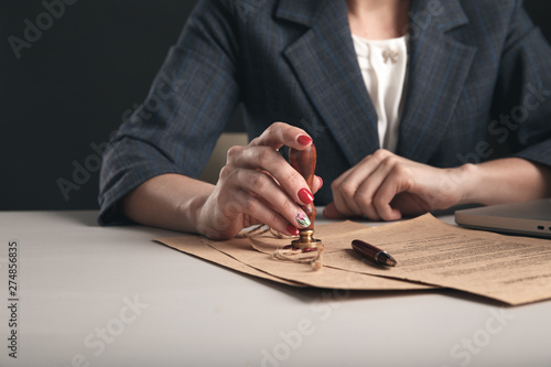 Fotografía Woman notary with paper documents and pen sitting at the desk