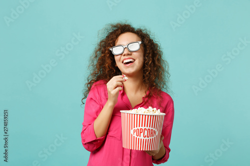 Laughing african girl in 3d imax glasses watching movie film and holding popcorn isolated on blue turquoise wall background in studio Wallpaper Mural