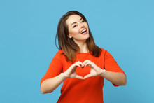 Beautiful Brunette Young Woman Wearing Red Orange Dresss Howing Shape Heart Sign With Hands, Isolated Over Blue Wall Background, Studio Portrait. People Lifestyle Fashion Concept. Mock Up Copy Space.