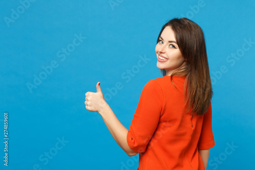 Photo  Back view brunette young woman wearing red orange dressshowing thumb up standing posing isolated over trendy blue wall background, studio portrait