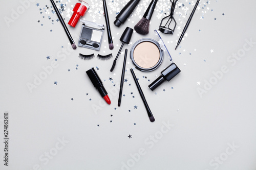 Poster Montagne Beauty products and cosmetic for woman makeup decorated star confetti on gray table top view. Flat lay style.