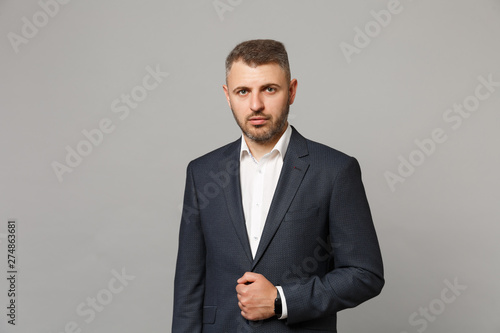 Fototapeta Handsome successful confident young business man in classic black suit shirt posing isolated on grey wall background, studio portrait. Achievement career wealth business concept. Mock up copy space. obraz na płótnie