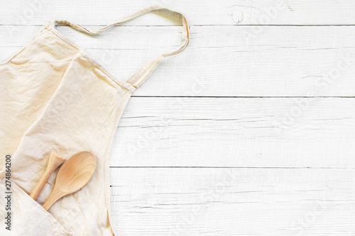 Fotografiet White wooden background with light linen apron