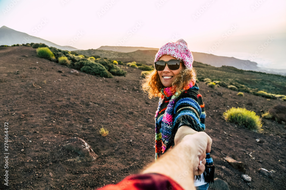 Fototapety, obrazy: Beautiful cheerful adult young woman smile and holding man hand during outdoor leisure activity trekking at the mountain - travel couple concept for active people - freedom holiday vacation in nature