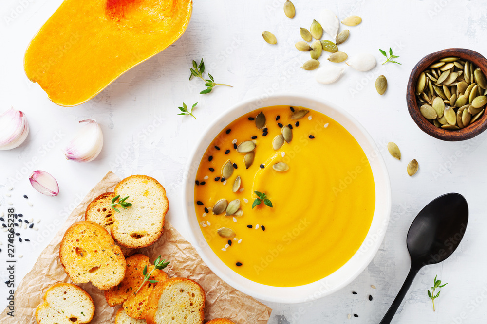 Fototapety, obrazy: Autumn pumpkin cream soup in bowl served with seeds and crouton on white stone table top view.