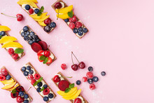 Low Calorie Snack Or Dessert From Sandwiches With Creamy Cheese And Summer Berry Fruits On Pink Trendy Background Top View. Flat Lay.