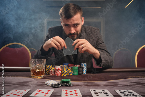 Fotografia Handsome bearded man is playing poker sitting at the table in casino