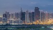 Jumeirah lake towers skyscrapers and golf course night to day transition timelapse, Dubai, United Arab Emirates. Aerial view from Greens district before sunrise
