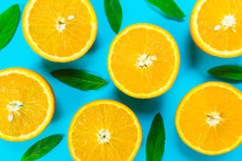 Colorful Picture Of Fresh Orange Slices And Mint Leaves On A Bright Blue Background. Top View