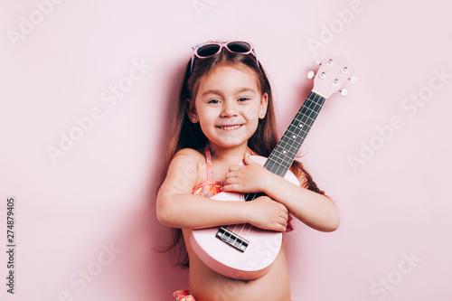 Cute little girl in swimsuit playing ukulele. - 274879405