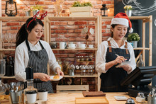 Two Asian Female Bartenders Dressed In Santa Hat And Working In Bar Counter In Christmas Holidays. Woman Barista Prepare Croissant While Coworker Waitress Taking Note On Customer Order In Xmas.