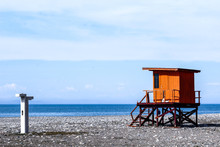 Wooden Lifeguard Tower. Orange Rescue Tower With Blue Sea And Sky On Background.