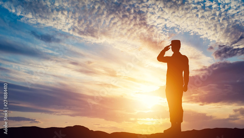 Obraz Soldier saluting at sunset. Army, salute, patriotic concept. - fototapety do salonu