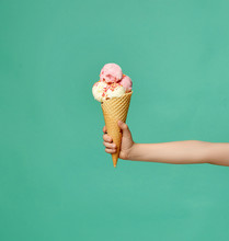 Baby Kid Hand Holding Big Ice-cream In Waffles Cone On Blue