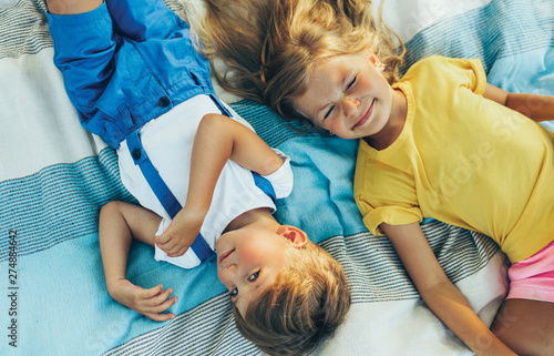 Poster Attraction parc Top view of adorable children, sister and brother lying on the blanket, looking to each other. Happy little boy and little girl enjoying summertime in the park. Candid shot of kids playing outdoors