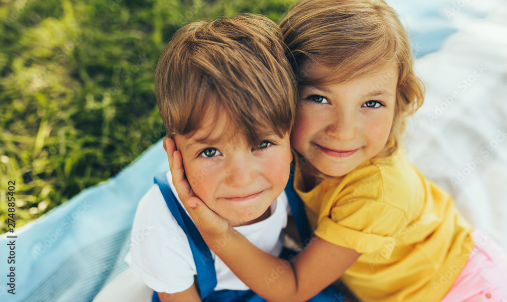 Fototapety, obrazy: Close up portrait of smiling two children playing on the blanket outdoors. Sister hugging her little brother in the park. Kids having fun on sunlight.