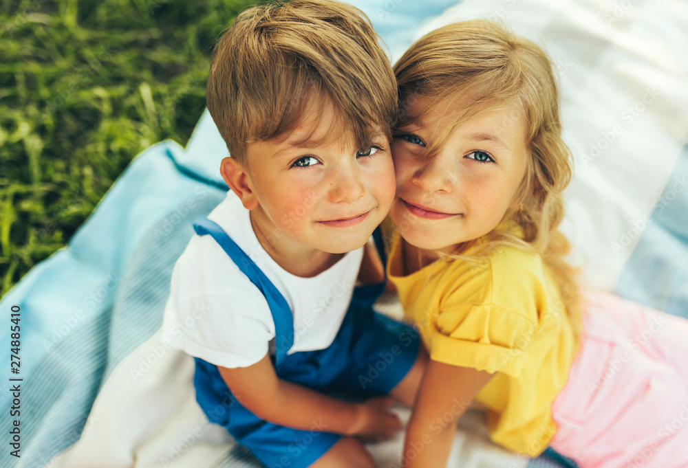 Fototapety, obrazy: Outdoors close up portrait of smiling two children playing on the blanket outdoors. Little boy and cute little girl bonding and relaxing in the park. Kids having fun on sunlight. Sister and brother