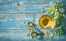 Cup Of Herbal Tea With Chamomile Flowers On Aged Blue Wood Plank