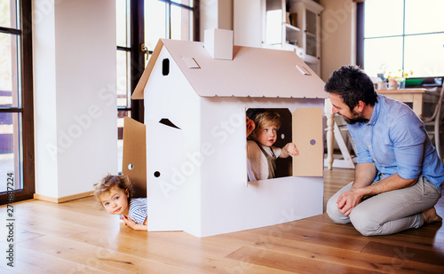 Foto Two toddler children with father playing with paper house indoors at home