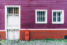 Building Facade Background With Purple Wood Wall, Red Brickwork And White Windows And A Door On The Street In Istanbul.