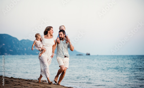 Poster Individuel Young family with two toddler children walking on beach on summer holiday.