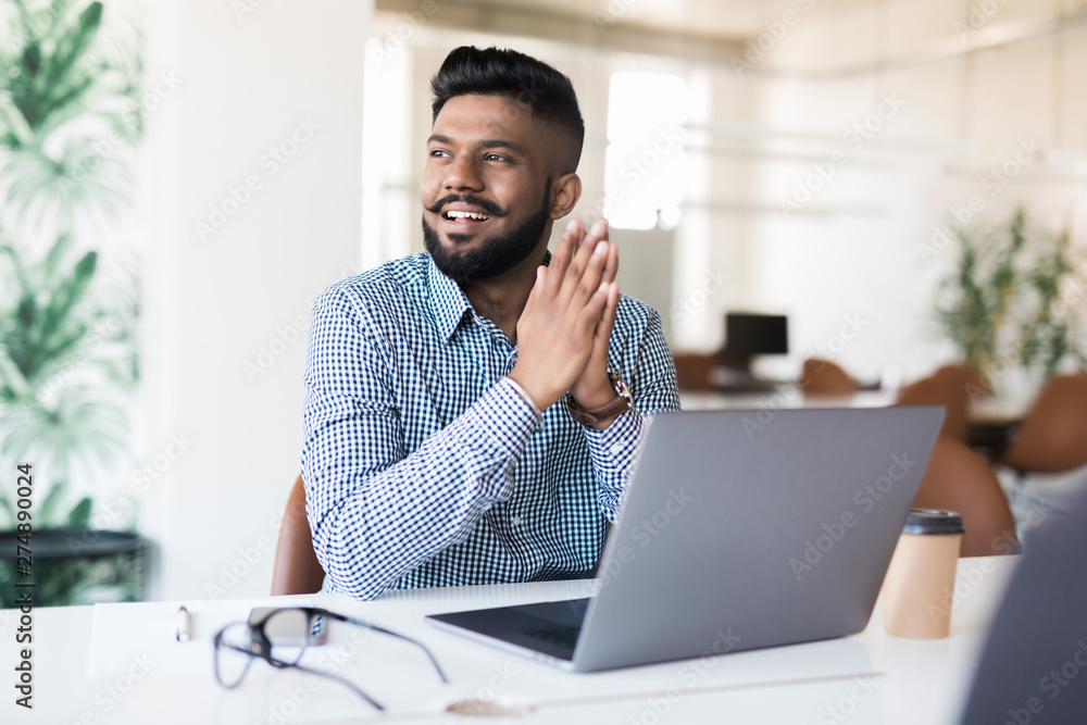 Fototapeta Young Asian Indian businessman working on laptop in modern office