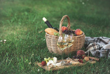 Picnic Setting With  White Wine,  Cheese, Fruits And Nuts. Outdoor Dinner On A  Green Lawn