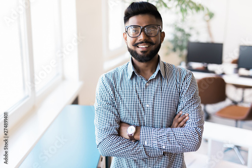 Fotografie, Obraz  Portrait of smiling Indian man crossed arms standing at modern office