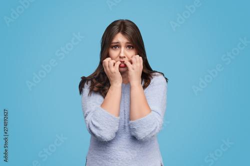 Obraz na plátně Hungry plump woman biting nails