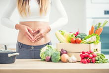 Woman With Sports Figure On Her Belly Shows Heart Shape In Home Kitchen With Wooden Box Full Of Organic Vegetable