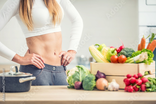 Stampa su Tela Woman with sports figure home kitchen with wooden box full of organic vegetable