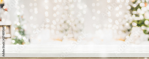 Empty white wold table top with abstract warm living room decor with christmas tree string light blur background with snow,Holiday backdrop,Mock up banner for display of advertise product.