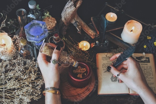Canvas Print A witch casting a spell and writing it down in her Book of Shadows with a green black feather and ink