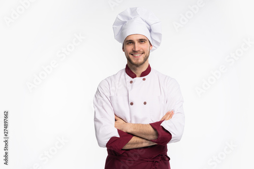 Fototapeta Portrait of positive handsome chef cook in beret and white outfit isolated on white background. obraz