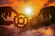 A pair of gears in the hands of people against the sunset, the evening sky. mechanism, the point of contact.