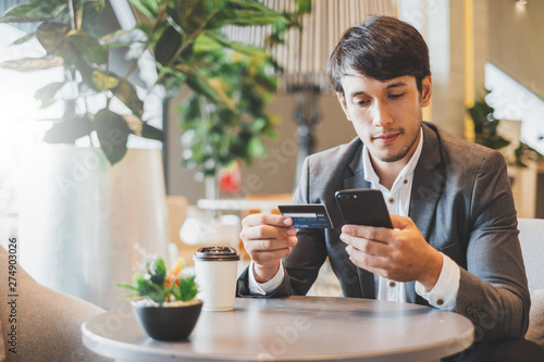 fototapeta na lodówkę Asian businessman using credit card and mobile phone for online financial payment and shopping
