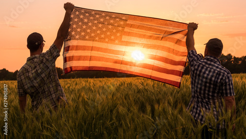 Foto auf AluDibond Rotglühen Two men energetically raised the US flag in a picturesque field of wheat
