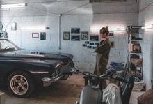 Attractive Caucasian Woman Looking At Her Vintage Old Car In A Garage