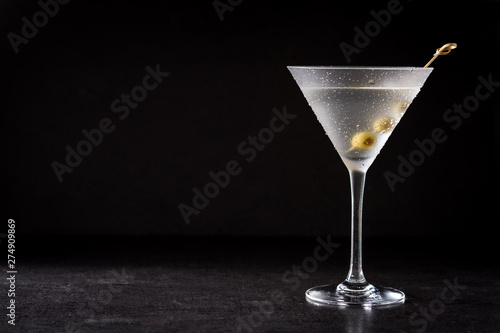 Photographie Classic Dry Martini with olives on black background. Copyspace