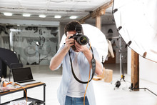 Portrait Of Young Brunette Photographer Man Shooting Model With Professional Camera In Studio