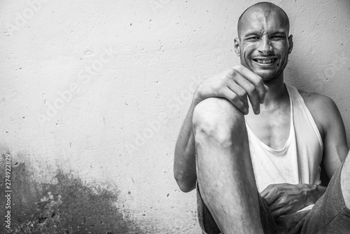 Poster de jardin Bar Young skinny anorexic bald positive and happy smiling homeless man sitting on the urban street in the city or town near white wall with big smile, homelessness social documentary concept