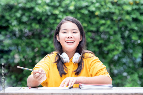 Smiling little Asian schoolgirl doing her homework in the park with headphones o Canvas-taulu