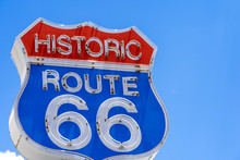 Red, White And Blue Neon Sign On The Famous, Historic Route 66 In Front Of Blue Sky