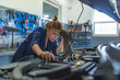 Female mechanic working under the hood of a car. Technician woman working in auto repair workshop. Female mechanic working on car. Repair, car service concept