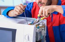 Young Repairman Fixing And Rep...