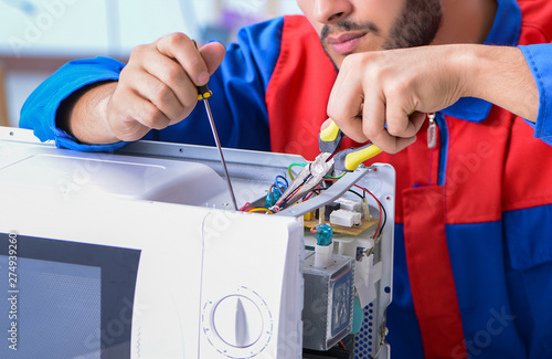 Fotografía  Young repairman fixing and repairing microwave oven