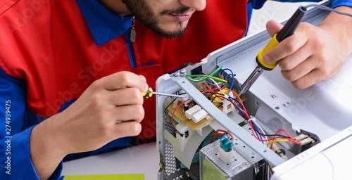 Fotomural  Young repairman fixing and repairing microwave oven