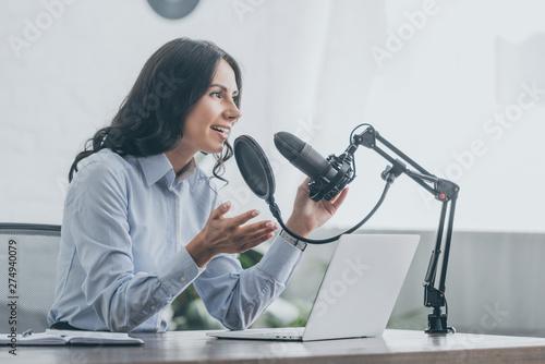 pretty radio host speaking in microphone and gesturing in broadcasting studio Canvas Print